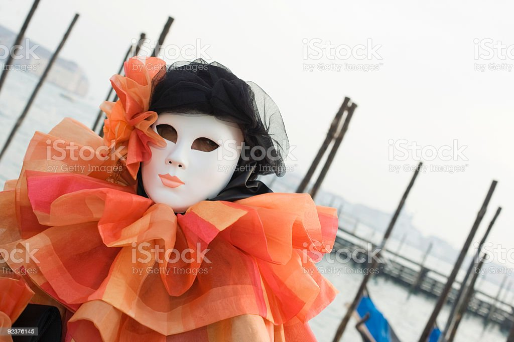 Tilt shot of mask with orange costume at Venetian Carnival royalty-free stock photo