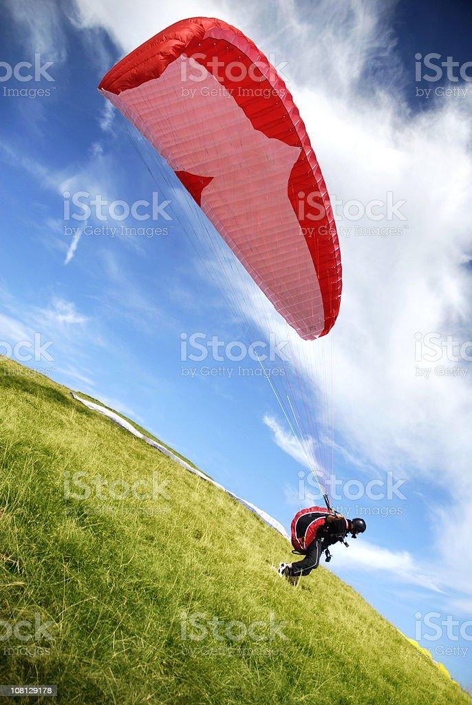 Tilt Shot of Paragliding Man Standing on Ground stock photo
