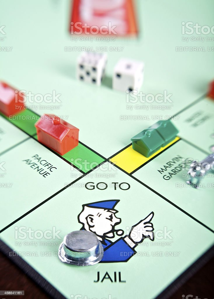 Tilted close-up of 'Go to Jail' on Monopoly board royalty-free stock photo