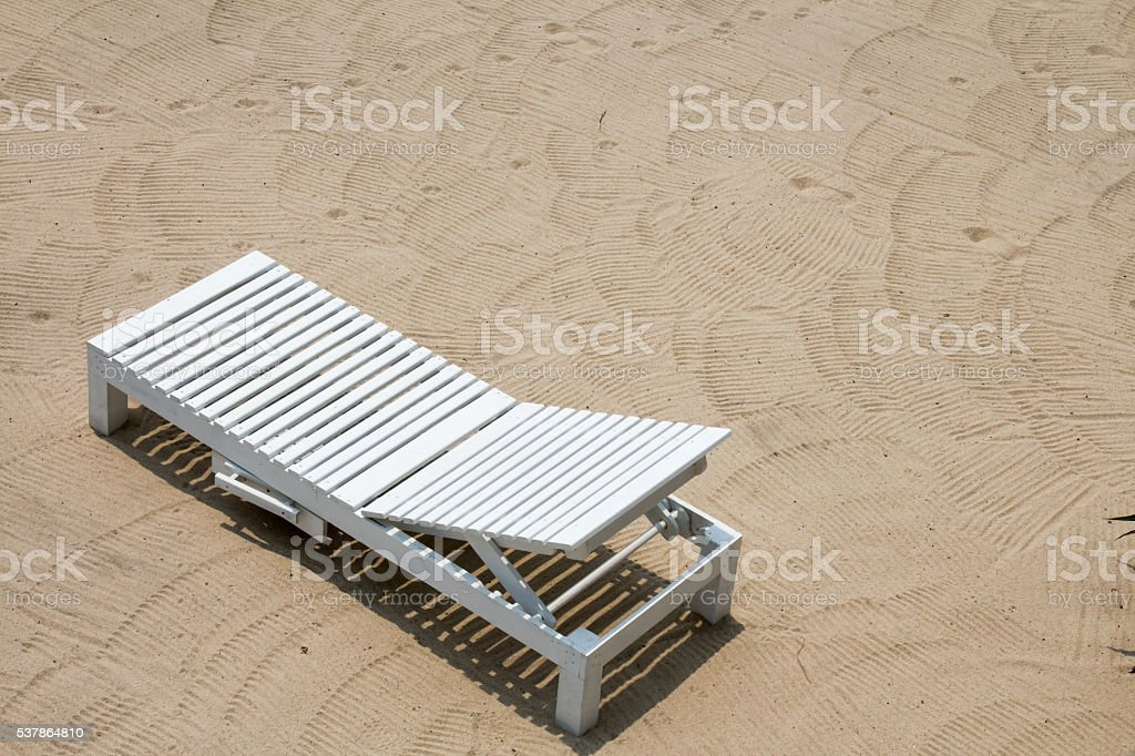 Tilted white wooden beach chair on sand stock photo