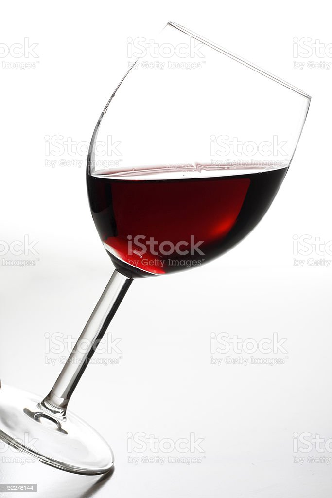 Tilted wine glass stock photo