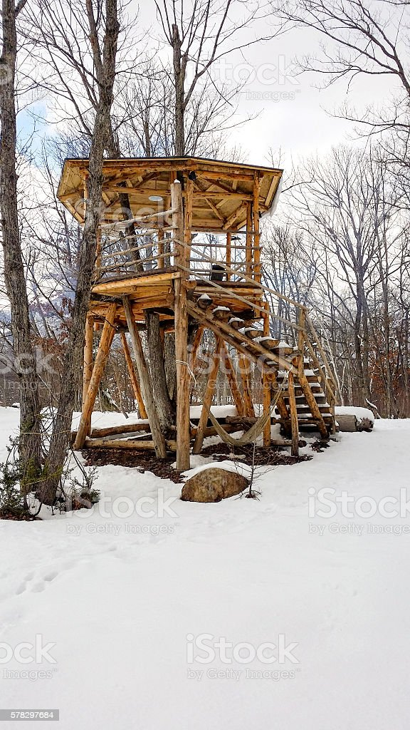 Timber fort structure in a rural snow setting with hammock stock photo