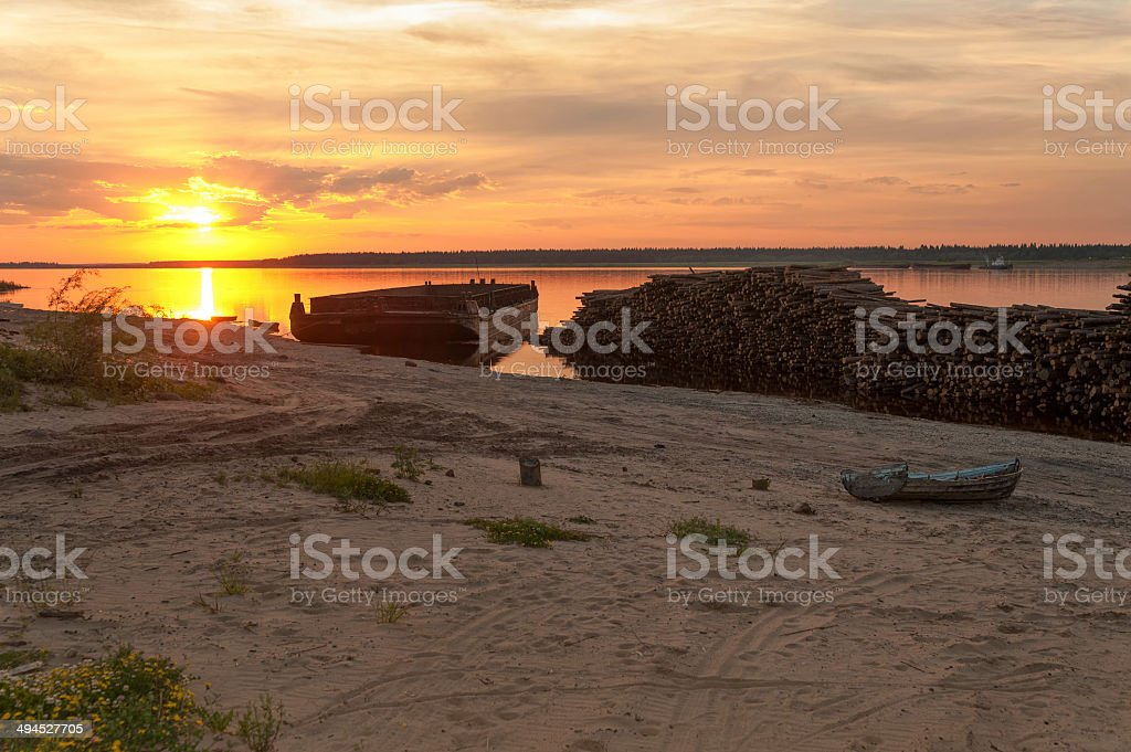 Timber store sinks in water before cargo ship at sunset stock photo