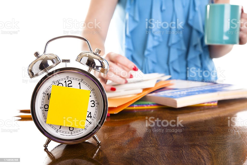Time:  Clock with sticky note on face, woman working background royalty-free stock photo