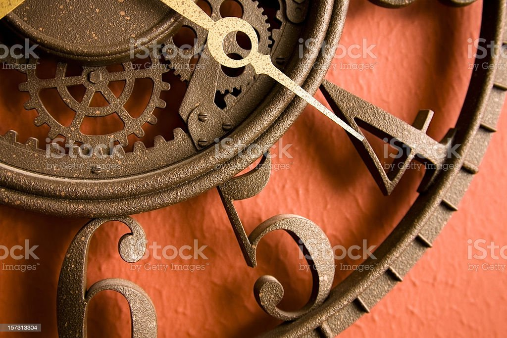 Time. Close-up of metal, rustic clock on red, rust wall. stock photo