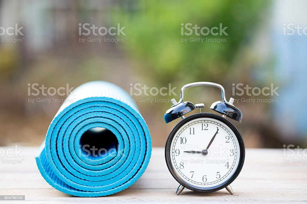 Time for exercising clock and yoga mat, outdoor stock photo