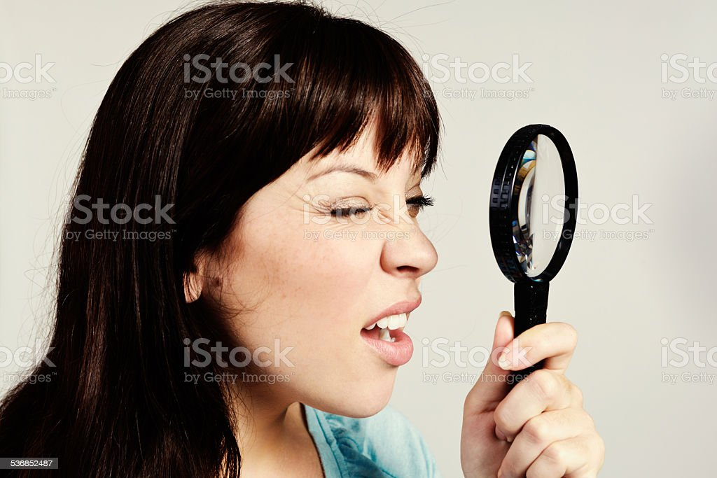 Time for optometrist visit! Pretty brunette squints through magnifying glass stock photo