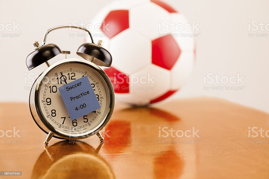 Time for Sports:  Alarm clock with soccer practice reminder.  Ball. stock photo