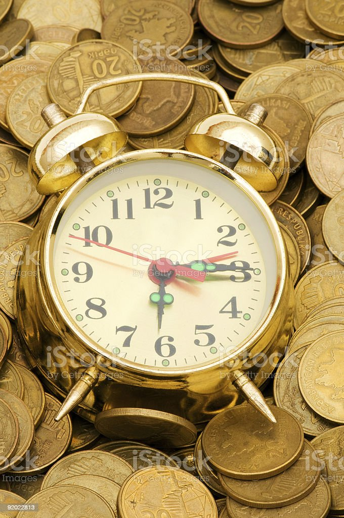 Time is money concept with clock and coins royalty-free stock photo