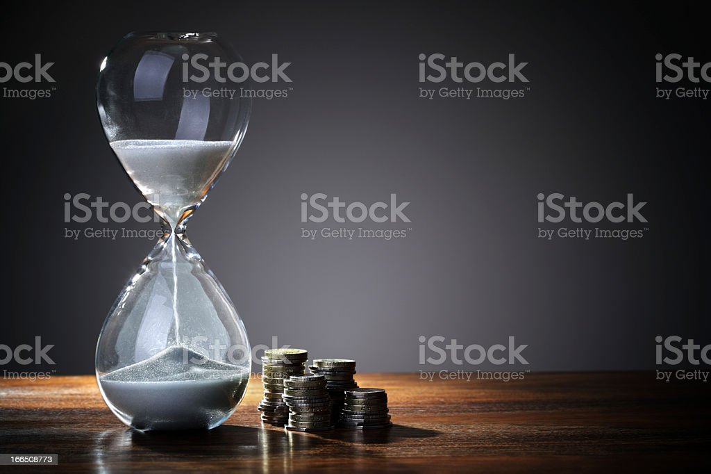 Time is money concept with hourglass next to stacks of coins stock photo
