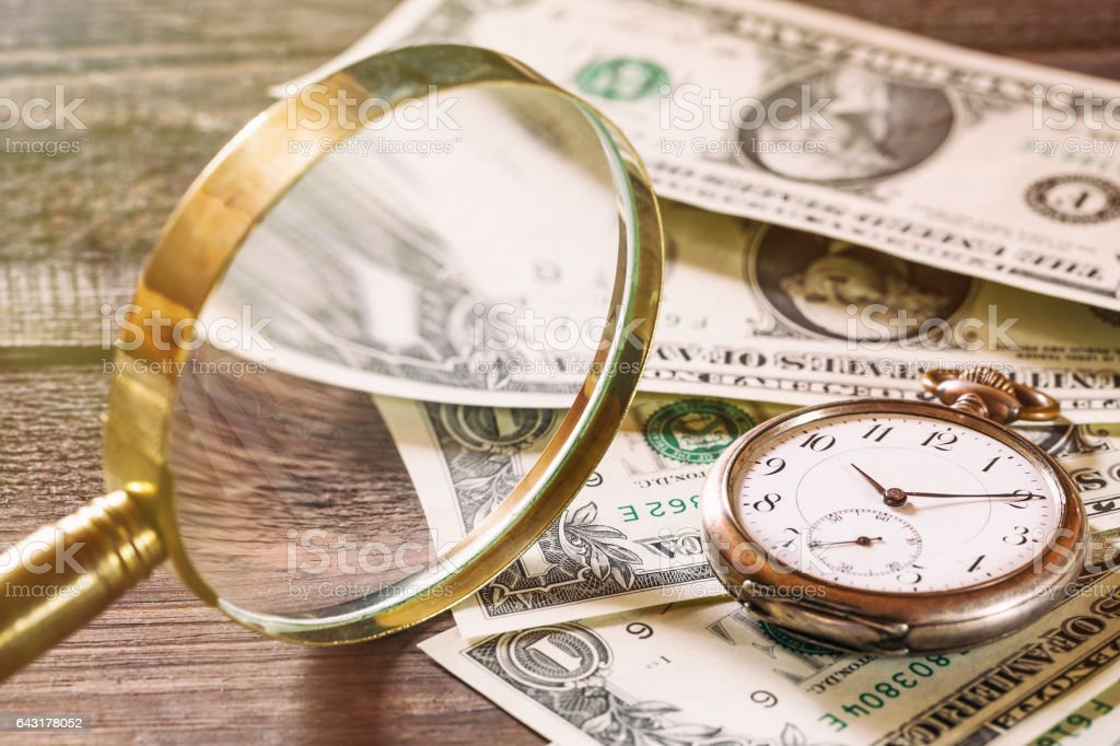 Time is money finance concept with old vintage clocks, dollar bills and magnifying glass on wooden table stock photo