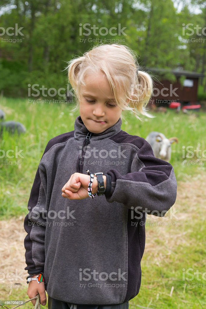 Time is up. Young boy checking his watch. stock photo