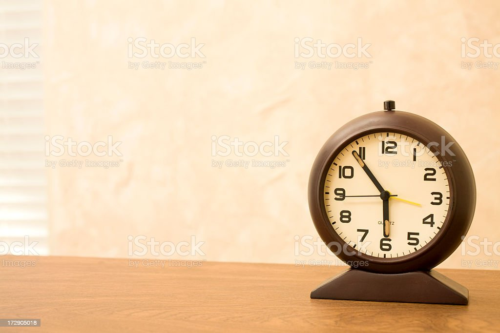 Time.  One alarm clock sitting on table stock photo