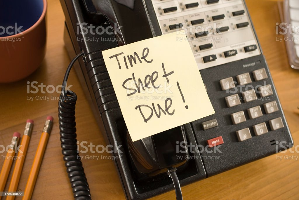 Time sheet due written on a sticky note stuck to a telephone stock photo