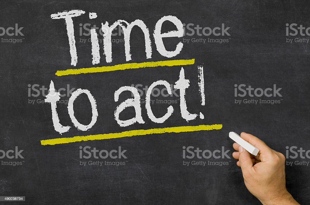 Time to act written on a blackboard stock photo