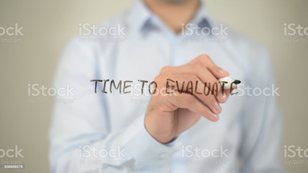 Time To Evaluate, man writing on transparent screen stock photo