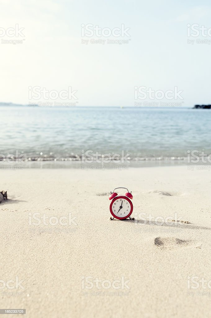 Time to go on vacation - clock on a beach royalty-free stock photo
