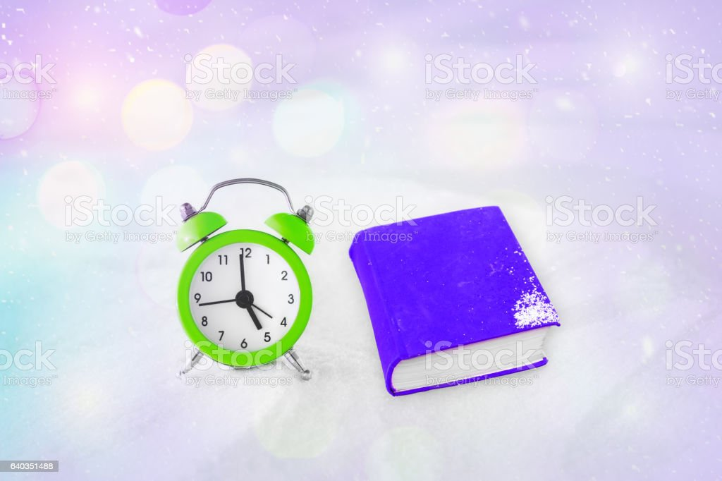 Time to read. Book and vintage alarm clock stock photo