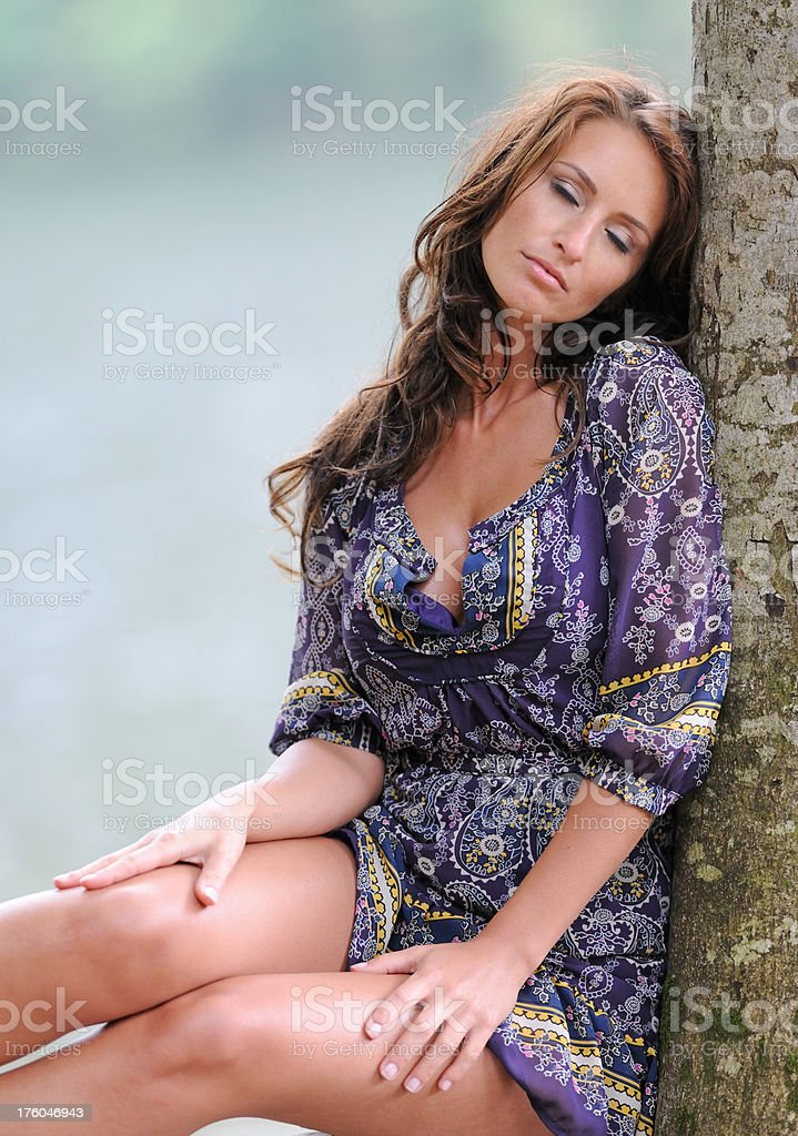 Time to relax - Beautiful woman leaning on a tree royalty-free stock photo