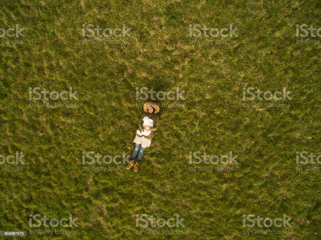 Aerial view of a woman and her white dog,taken with drone