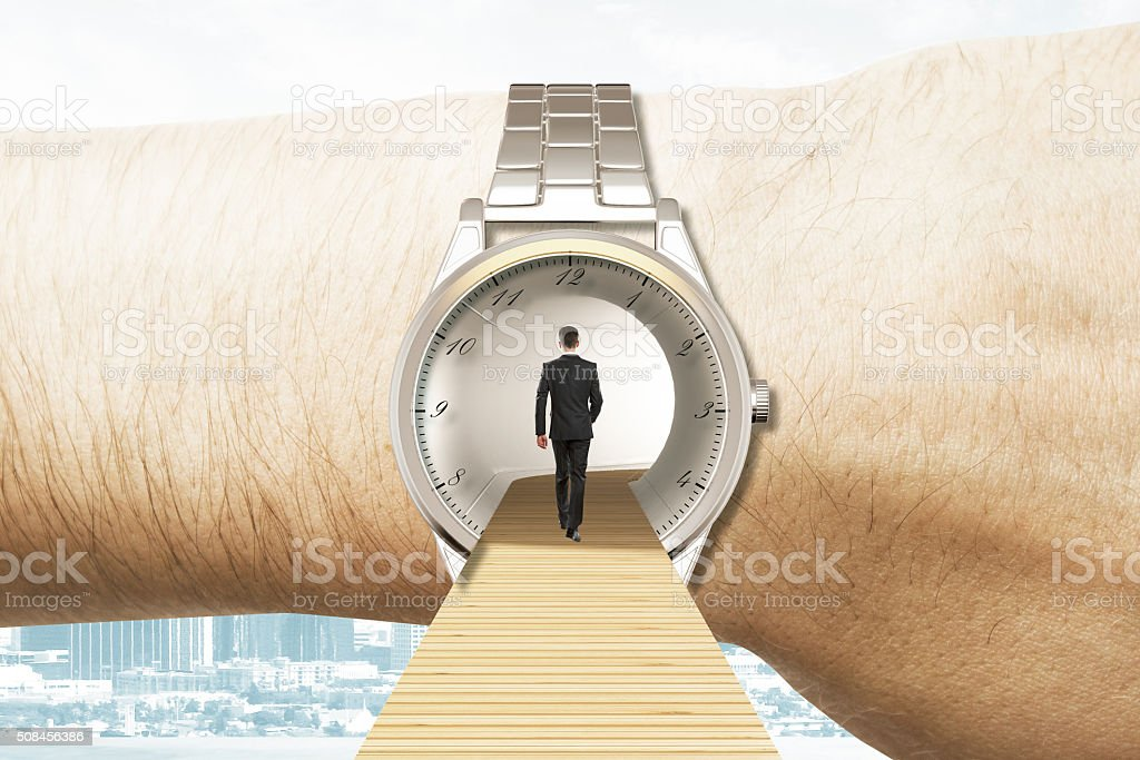 Time travel concept with businessman walking into the watches on stock photo