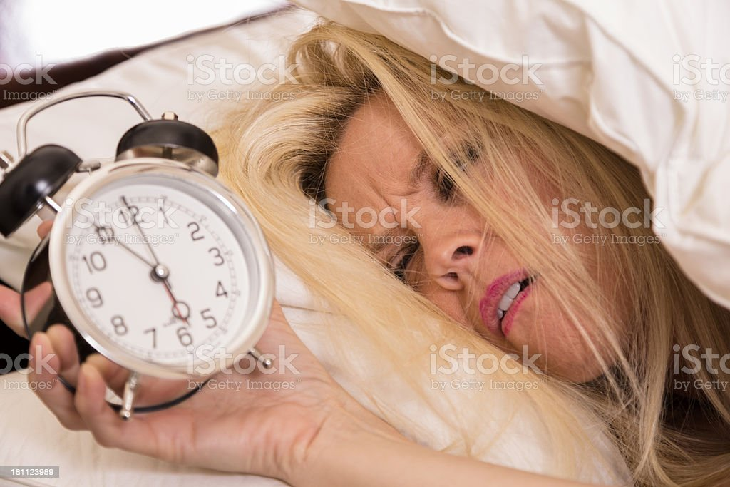 Time: Woman does not want to wake for alarm clock. royalty-free stock photo