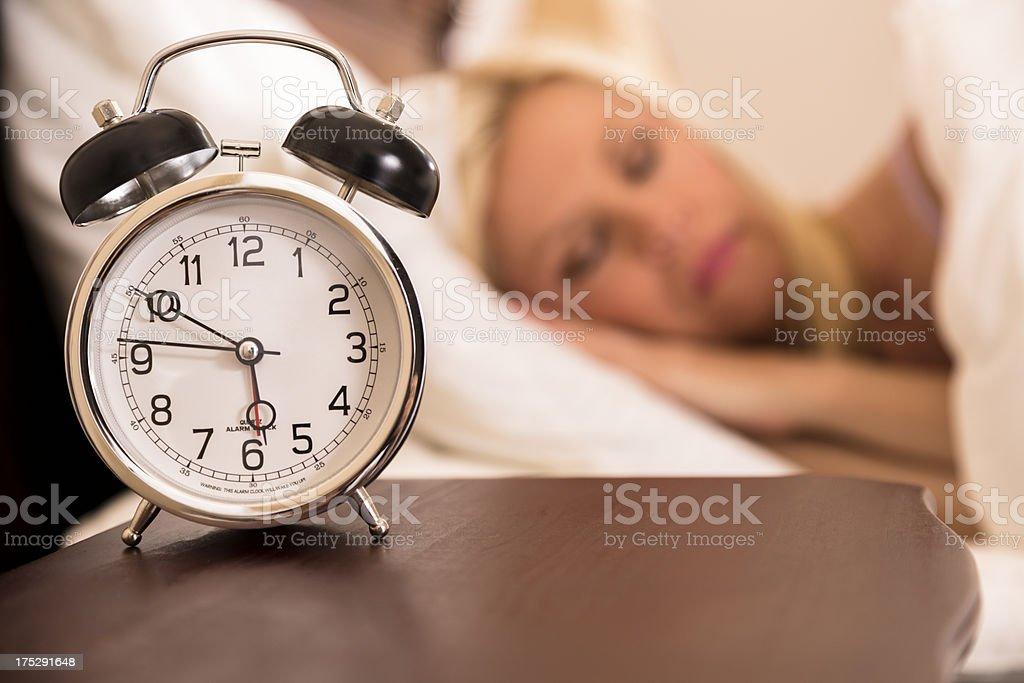 Time: Woman sleeping.  Alarm clock goes off soon. stock photo