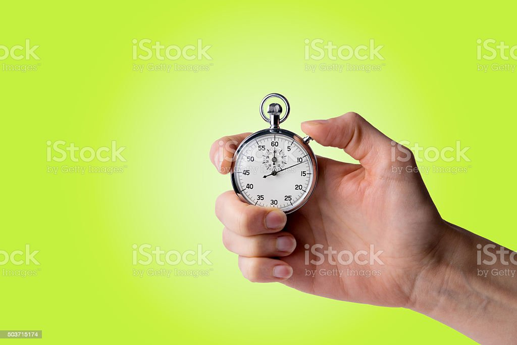 timer hold in hand, button pressed yellow green background stock photo