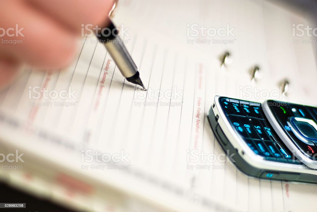 Timetable , pen and telephone stock photo