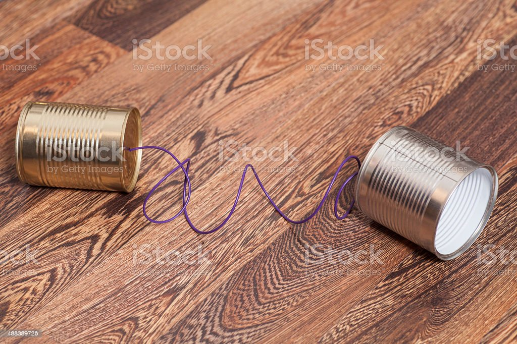Tin Can Phone on Wooden Background.Communication concept stock photo