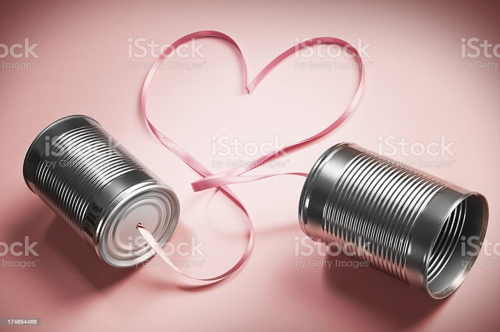 Tin can telephones connected with heart shaped ribbon royalty-free stock photo