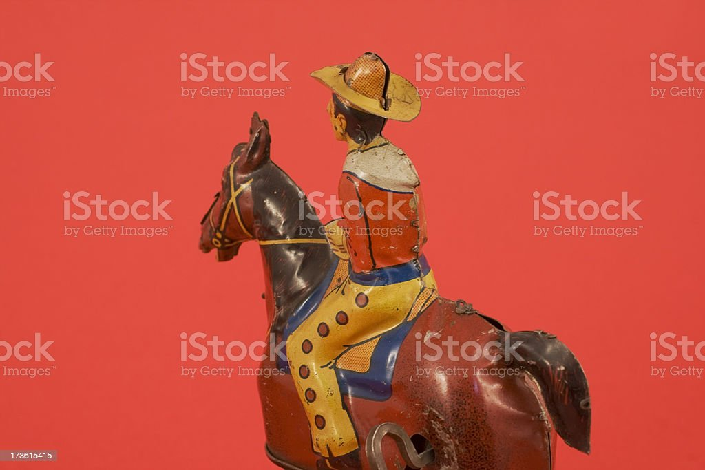 Tin toy cowboy with hat and horse on red background. stock photo