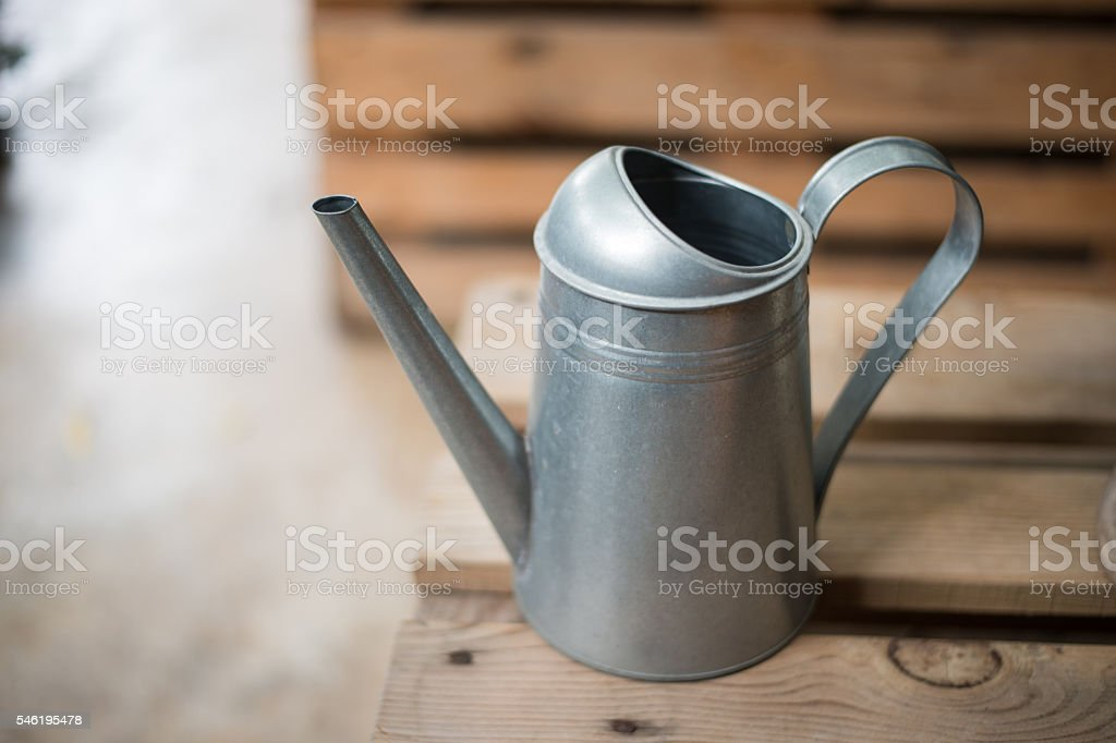 tin watering can on wooden chair stock photo