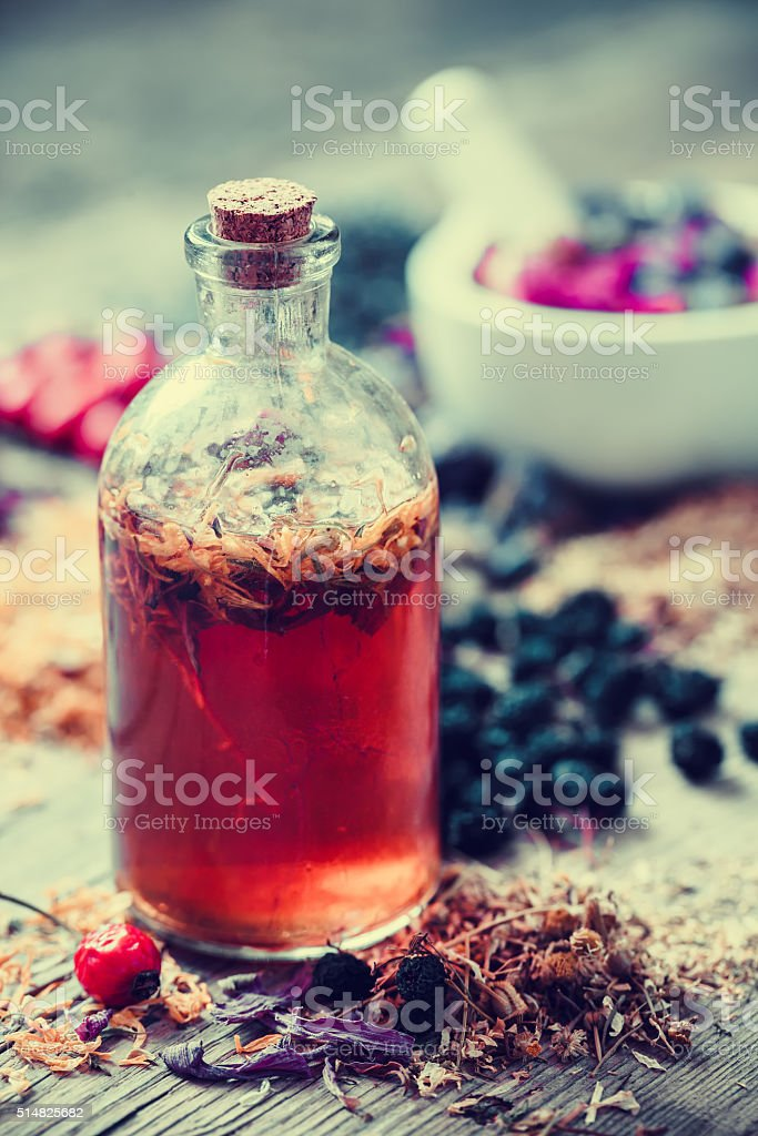 Tincture bottle and mortar of healing herbs on background. stock photo