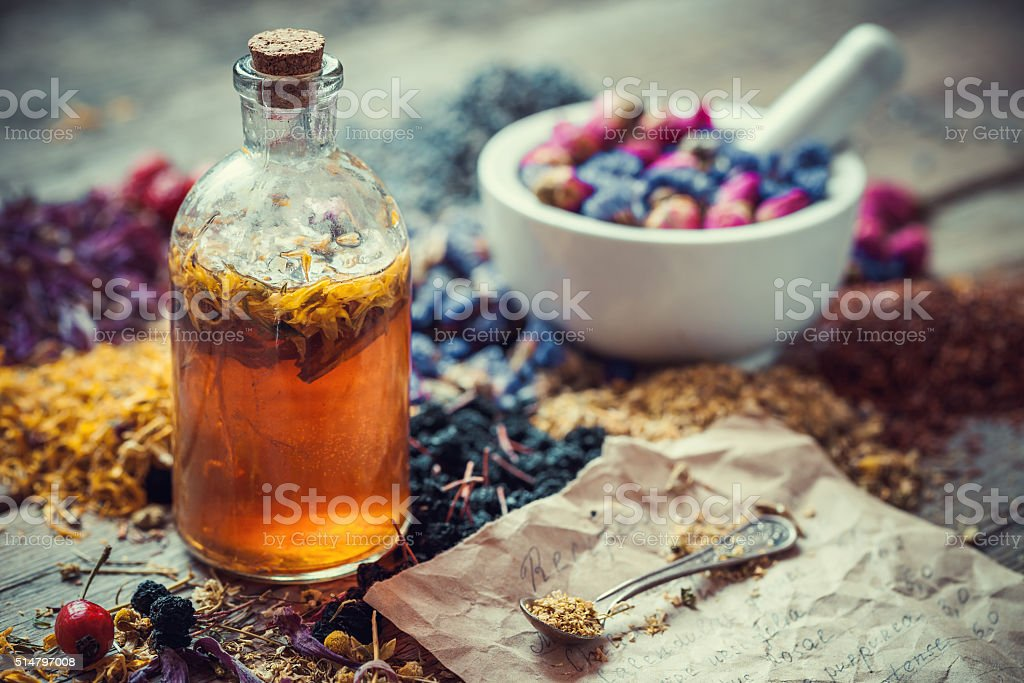 Tincture bottle, mortar of healing herbs and paper of recipes stock photo