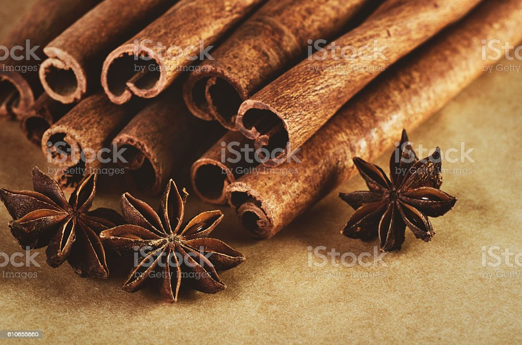 tinted image cinnamon sticks and three stars anise on paper stock photo
