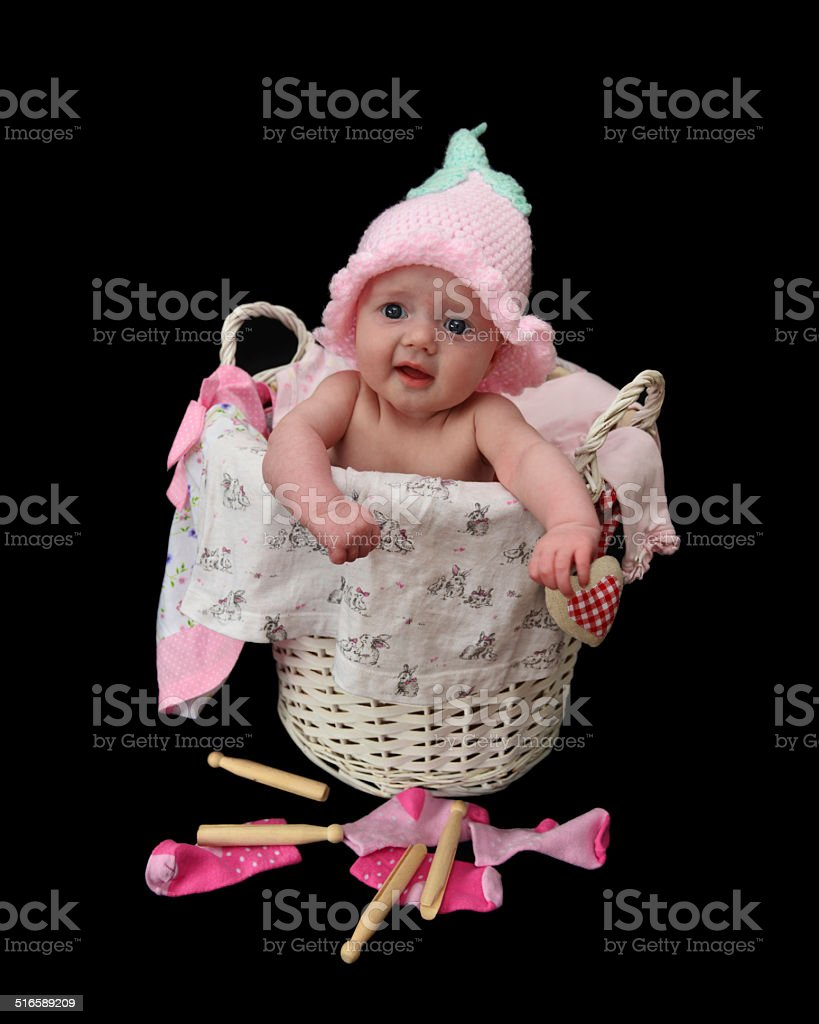Tiny baby girl in a laundry basket stock photo