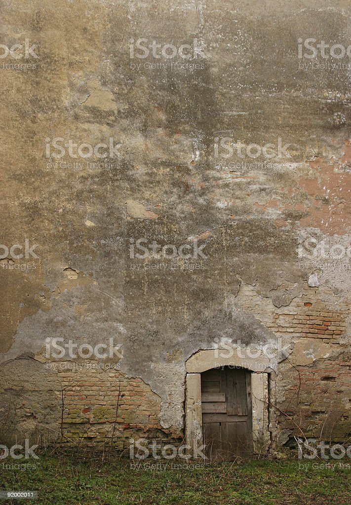 Tiny backdoor and facade of an old abandoned building stock photo