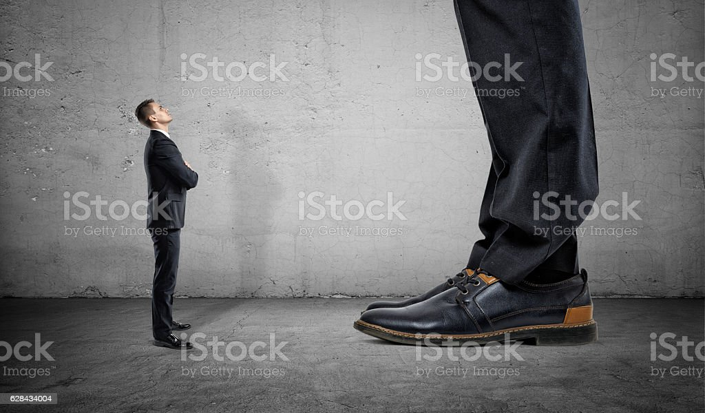 Tiny businessman looking up on huge legs of another man stock photo