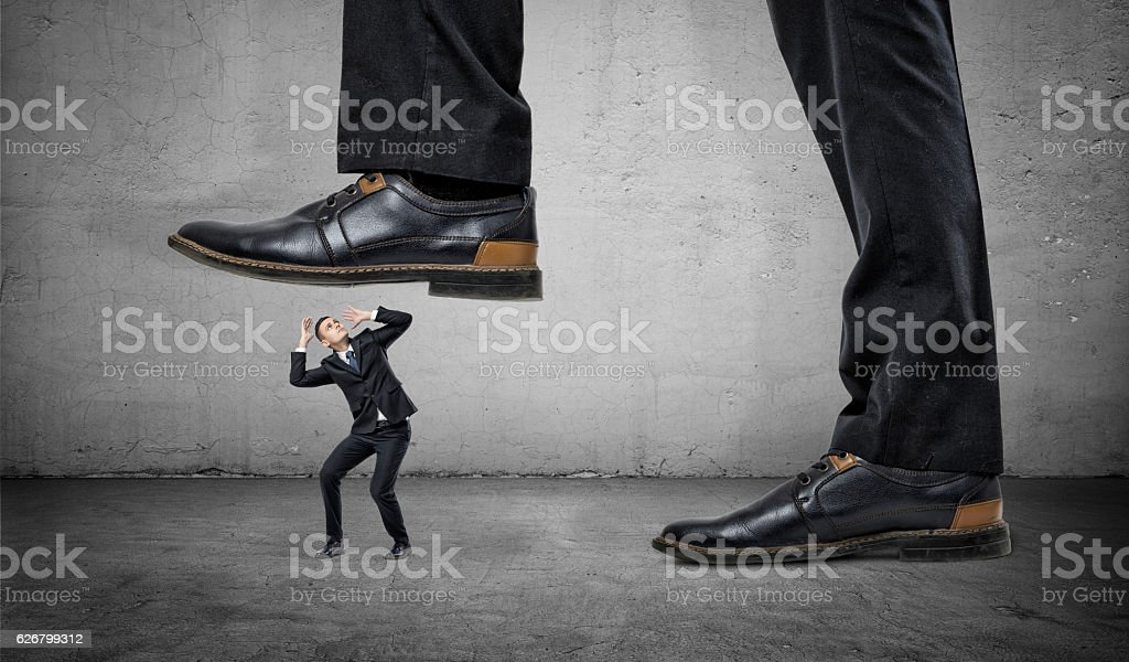 Tiny frightened businessman under feet of huge man stock photo