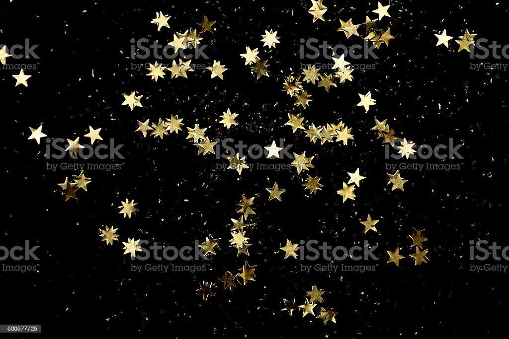Tiny golden star shapes on black background stock photo