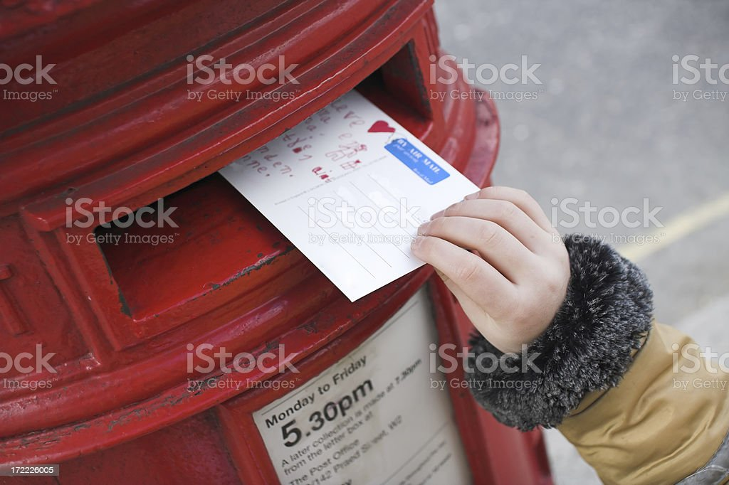 Tiny hand pushing a postcard inside a postbox stock photo