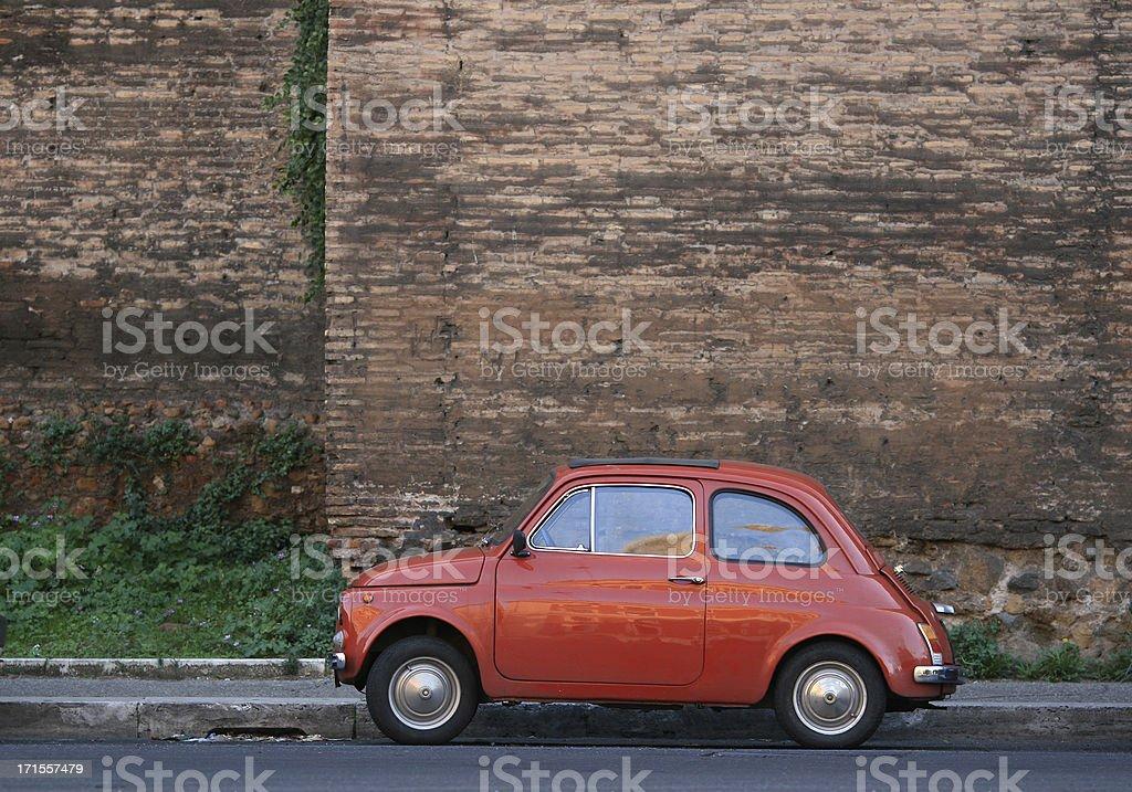 Tiny Italian car in front of Rome's city wall. royalty-free stock photo