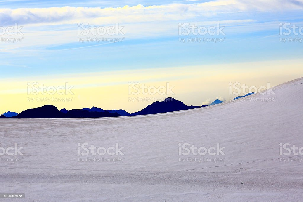 tiny mountaineer hiking on Breithorn Theodul glacier plateau – Swiss Alps stock photo