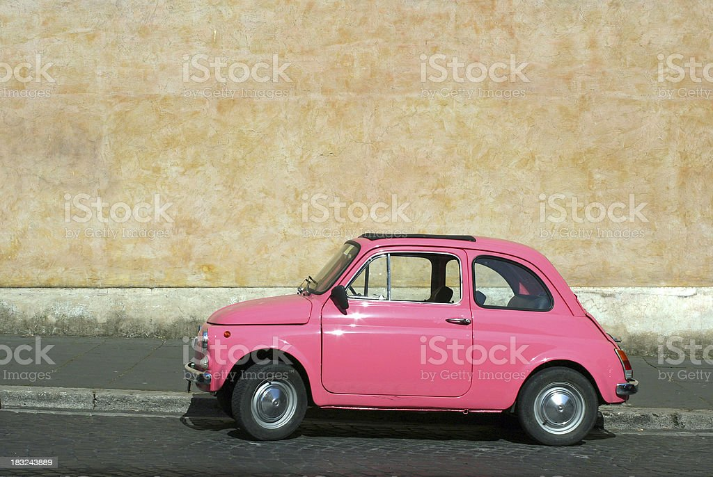Tiny pink vintage car in Rome, Italy royalty-free stock photo