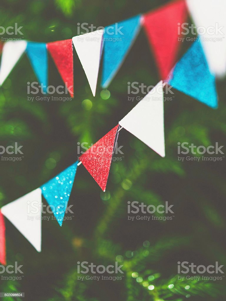 Tiny red, white and blue bunting hanging on Christmas tree stock photo