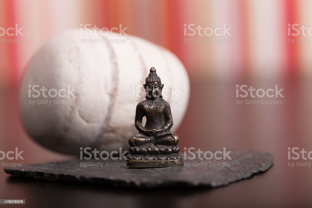 Tiny Statue of Buddha in the Lotus Position stock photo