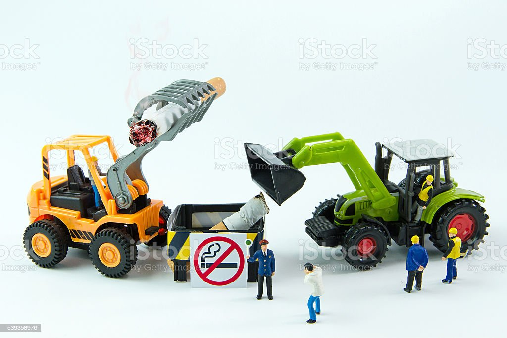 Tiny toys destroy cigarette.Concept No Smoking Day. stock photo