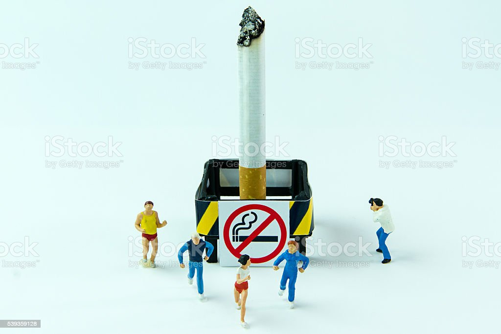 Tiny toys scamper cigarette.Concept No Smoking Day. stock photo