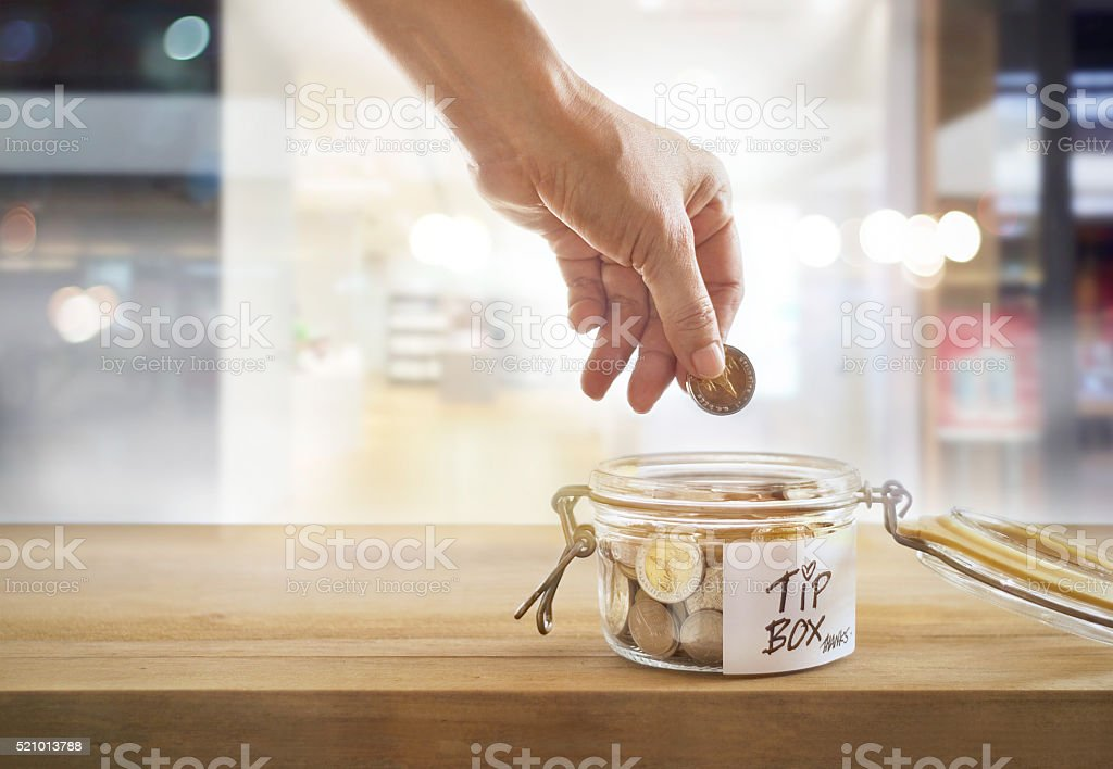 Tip box, coin in the glass bowl in cafe front stock photo